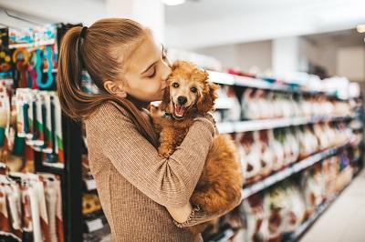 ドッグフード売り場で犬にキスする女性